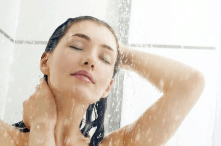 Beautiful woman showering with hot water from new plumbing and hot water heater installation